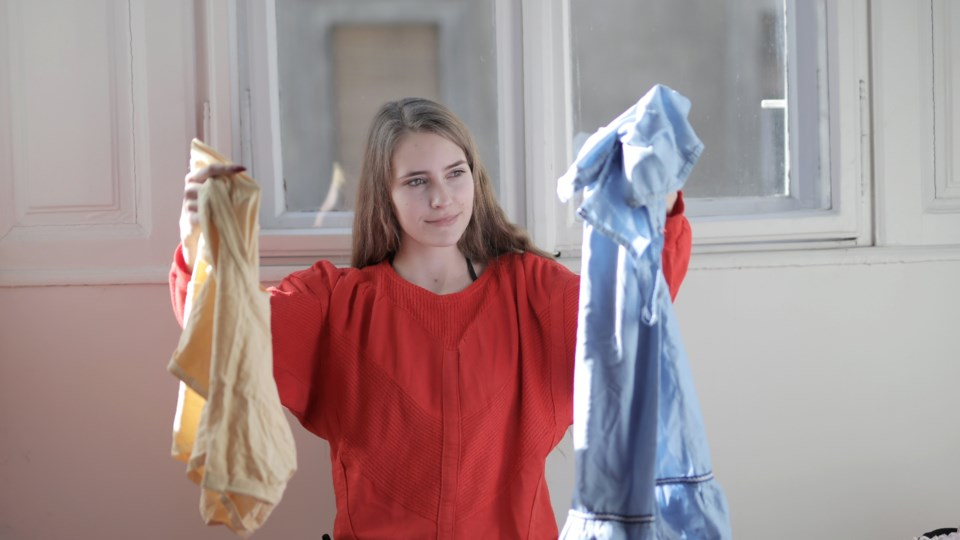 woman-in-red-long-sleeve-shirt-holding-her-clothes-3794129